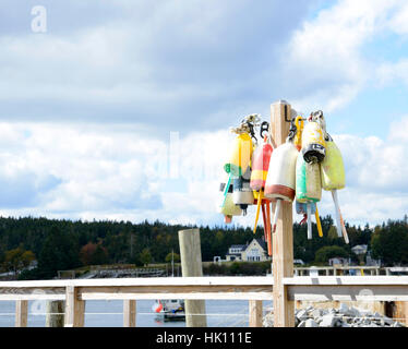 many old lobster buoys on a wooden post - Stock Photo