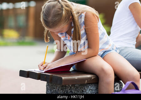 student girl writing to notebook at school yard - Stock Photo