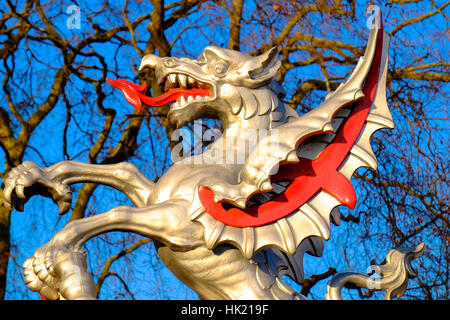 A silver and red dragon sculpture shines in the sun - Stock Photo