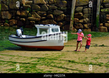 Two small children playing on the seashore and pulling on a rope from a motorboat at low tide  Mousehole Harbour, - Stock Photo