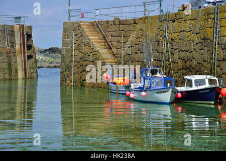 Small fishing boats moored against the harbour wall in the picturesque fishing village of Mousehole on the south - Stock Photo