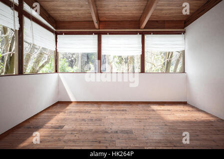 Empty room with white walls, wooden floor and ceiling with beams, with lots of windows and trees outside. 3d rendering. - Stock Photo
