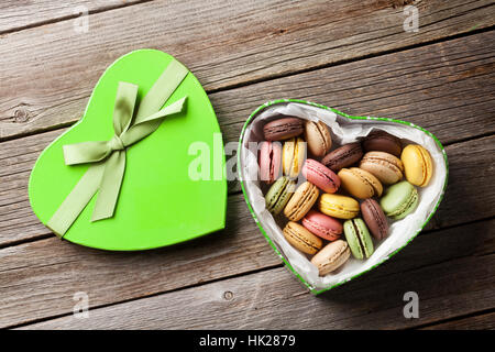 Colorful macaroons in Valentines day heart shaped gift box on wooden table. Top view - Stock Photo