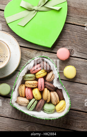 Colorful macaroons in Valentines day heart shaped gift box and coffee cup on wooden table. Top view - Stock Photo