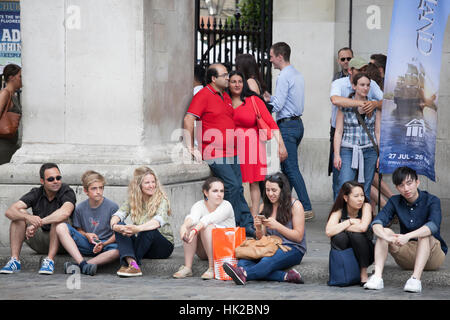 LONDON, ENGLAND - JULY 12, 2016 A motley crowd sitting on the pavement for rest. Happy couple in red in the center - Stock Photo