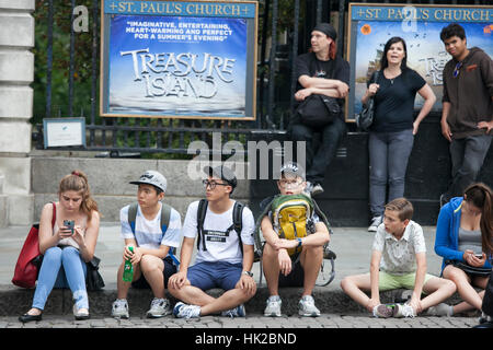 LONDON, ENGLAND - JULY 12, 2016 A motley crowd sitting on the pavement for rest - Stock Photo
