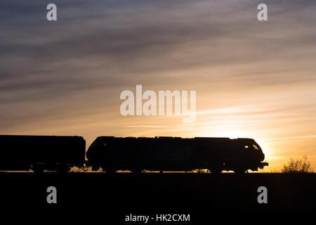 Class 68 diesel locomotive pulling a Chiltern Railways Mainline train, silhouetted at sunset, Warwickshire, UK - Stock Photo