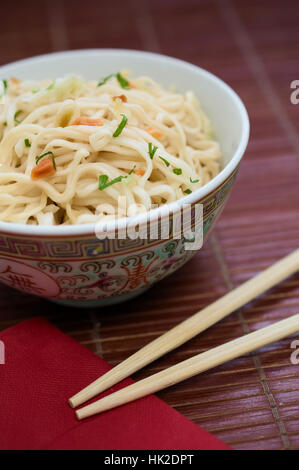 Concept of asian food. Traditional Chinese pasta ramen noodles in ceramic bowl with chinese chopsticks and red napkin - Stock Photo