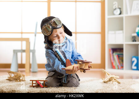 Little kid boy dreams be an aviator and plays with toy airplanes sitting on floor in nursery room - Stock Photo