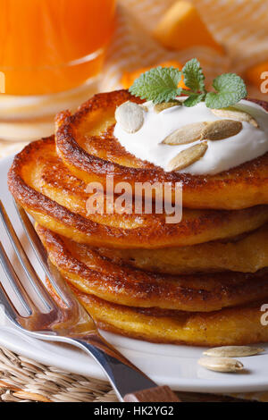 Delicious pumpkin pancakes with sour cream close-up on the table. vertical - Stock Photo