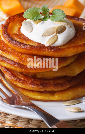 pumpkin pancakes with sour cream, mint and seeds macro on the table. vertical - Stock Photo