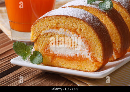 Tasty dessert of carrot roll with cream closeup on table - Stock Photo