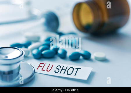 closeup of the desk of a doctors office with a stethoscope a bottle with pills a piece of paper with the text flu - Stock Photo