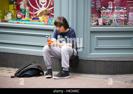 LONDON, ENGLAND - JULY 12, 2016 Teenager sitting on the sidewalk near the store, waiting for friends - Stock Photo