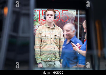 LONDON, ENGLAND - JULY 12, 2016 Young man with headphones listening to music and waiting for friends - Stock Photo