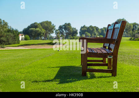 Wooden bench on a sunny day in golf course - Stock Photo