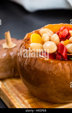 White bean and red pepper vegetables stew in pumpkin bowls served on wooden board - Stock Photo