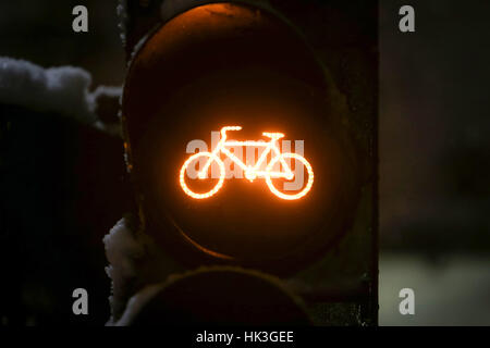 A close up of scoreboad showing yellow light for bicycles during snowfall. - Stock Photo