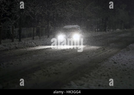 A car driving on the road in the aggravated traffic due to strong snowfall. - Stock Photo