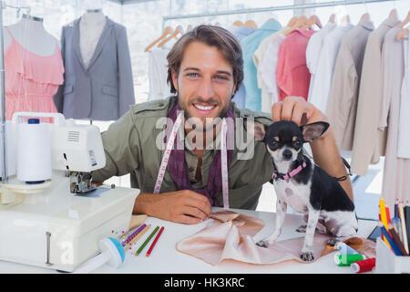 Fashion designer petting his cute chihuahua - Stock Photo