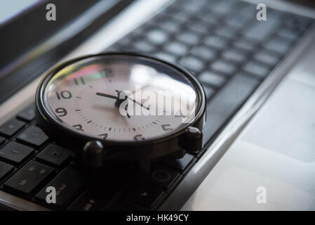 Black clock lay on keyboard time metaphor concept in dark low key tone, selective focus. - Stock Photo