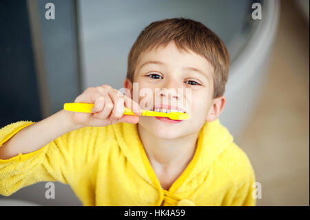 Boy brushing his teeth in bathtub, smiling. healthy lifestyle concept - Stock Photo