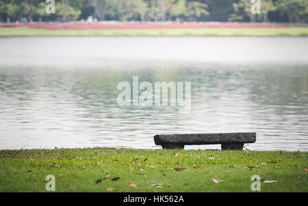 Flat stone seat on edge of grass floor near lagoon park. Grass covered by dry leaves. - Stock Photo