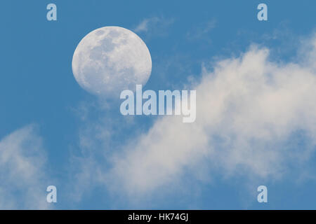 moon and clouds in daylight - Stock Photo