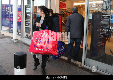 Arena Retail Park, Harringay, North London, UK. 26 Dec 2016 Shoppers hold multiple bags at Next in Arena Retail - Stock Photo