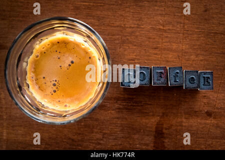 Espresso coffee with crema in round glass on a plywood timber background with rubber ink stamp lettering to the - Stock Photo
