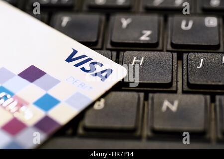 VISA payment debit card put on black keyboard. - Stock Photo