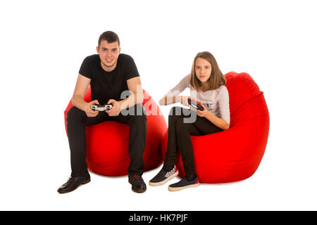 Young man and funny girl playing video games while sitting on red beanbag chairs isolated on white background - Stock Photo