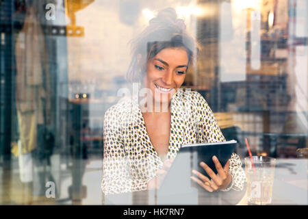 Woman using a Tablet pc in Coffee shop - Stock Photo