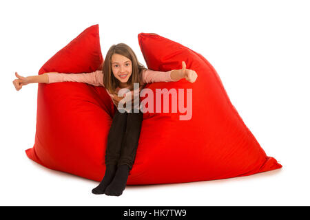 Happy girl sitting on red beanbag sofa for living room or other room isolated on white background - Stock Photo
