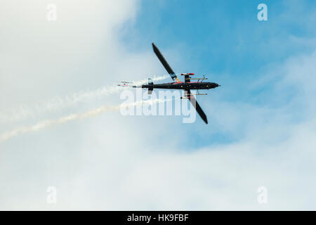 A helicopter, releasing smoke, is performing stunts in the air - Stock Photo