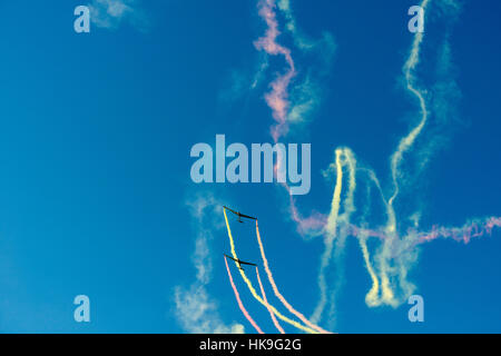 Two sailplanes, releasing smoke, are performing stunts in the air - Stock Photo