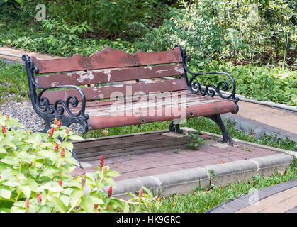 Empty old bench near the brick pathway in the botanical garden. - Stock Photo