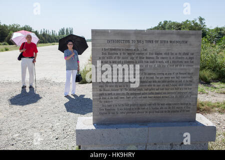 Two Chinese tourists read an information èanel at the entrance of Western Xia Imperial Tombs. Yinchuan, Ningxia, - Stock Photo
