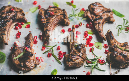 Grilled lamb ribs with pomegranate seeds, fresh mint and rosemary over metal baking tray background, selective focus, - Stock Photo