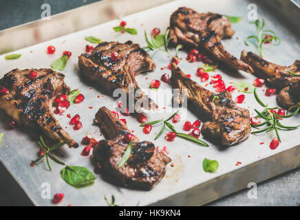 Grilled lamb ribs with pomegranate seeds, fresh mint and rosemary in metal baking tray, selective focus, horizontal - Stock Photo