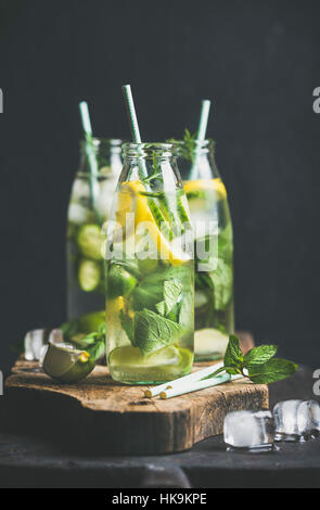 Citrus fruit and herbs infused sassi water for detox, healthy eating or dieting in glass bottles with straws, dark - Stock Photo