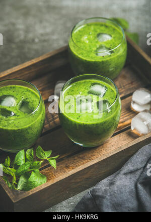 Fresh green smoothie in glasses with ice cubes, mint and lime in wooden tray over grey concrete background, selective - Stock Photo
