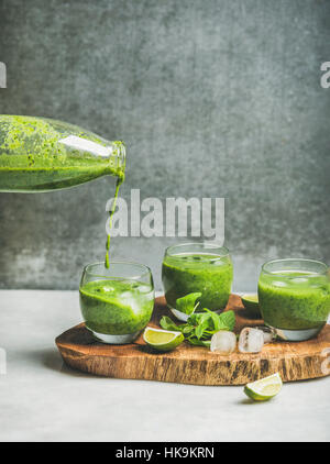 Fresh green smoothie in glasses and pouring from bottle with ice cubes, mint, lime on wooden board, grey concrete - Stock Photo