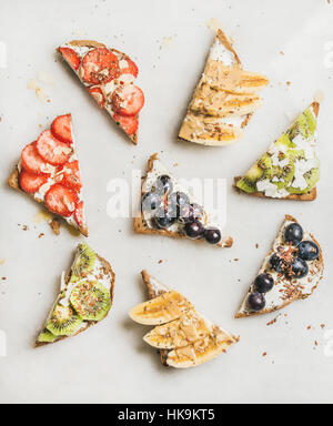 Healthy breakfast toasts cut in pieces. Wholegrain bread slices with cream cheese, various fruit, seeds and nuts. - Stock Photo
