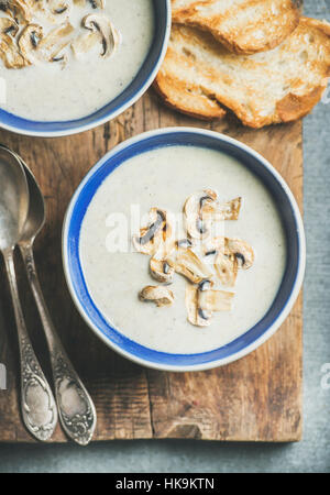 Close-up of creamy mushroom soup in bowls with toasted bread slices on rustic serving board over grey concrete background, - Stock Photo