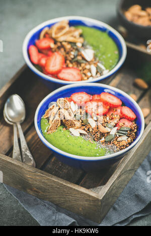 Healthy breakfast. Green smoothie bowls with fresh strawberries, granola, chia and pumpkin seeds, dried fruit and - Stock Photo