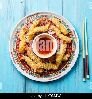 Deep fried breaded Tempura prawn shrimps with sauce on blue background - Stock Photo