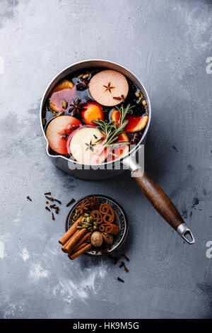 Mulled wine hot drink with citrus, apple and spices in aluminum casserole on concrete background - Stock Photo