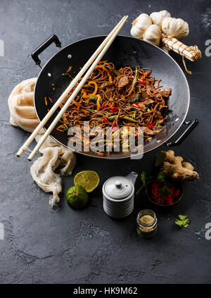 Asian fast food Stir fry noodles soba with beef and vegetables in wok pan on dark stone background - Stock Photo