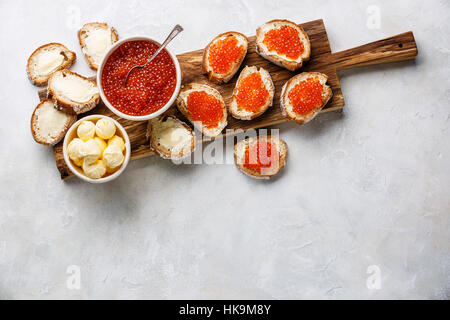 Salmon red caviar in bowl and Sandwiches on wooden cutting board on white background copy space - Stock Photo